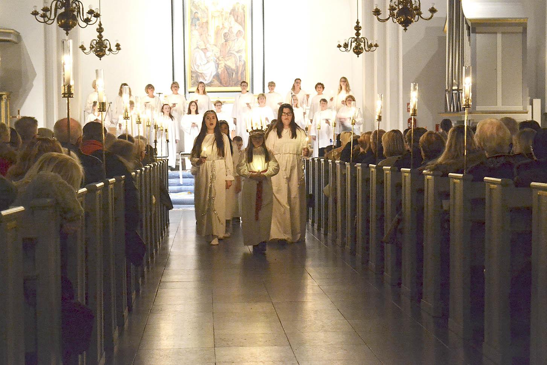 Lucian Amanda Söderberg skrider fram i Nybro kyrka tillsammans med sina tärnor och stjärngossar.